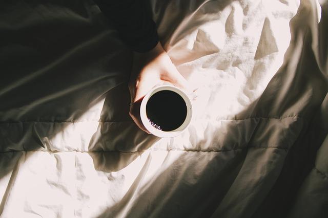 Človek drží hrnček s kávou položený na posteli.jpg