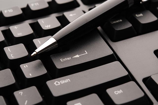 Čierna klávesnica na ktorej je čierne pero