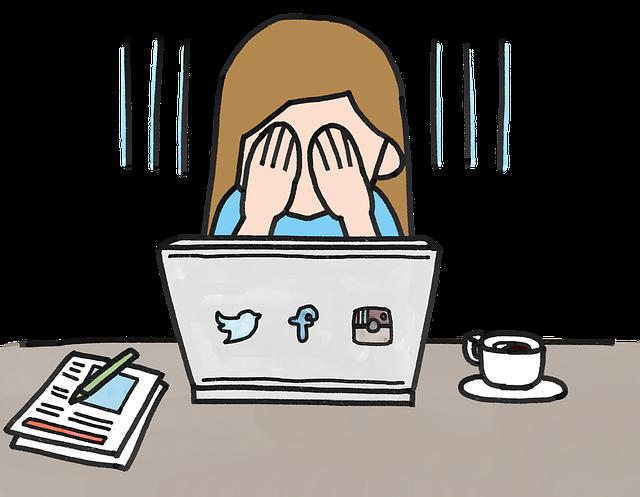 Postavička sedí za počítačom a má ruky na tvári