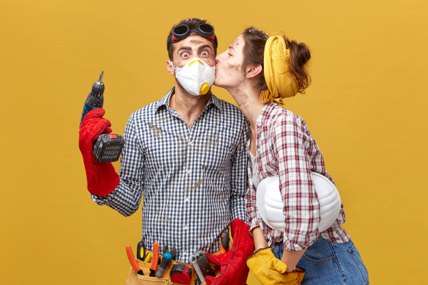 pretty-female-kissing-her-husband-cheek-being-thankful-him-repairing-her-wardrobe-surprised-male-worker-mask-holding-drilling-machine-being-glad-receive-kiss-from-his-girlfriend_273609-79